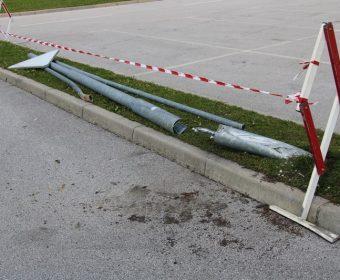 Poškodovan steber javne razsvetljave in prometni znak